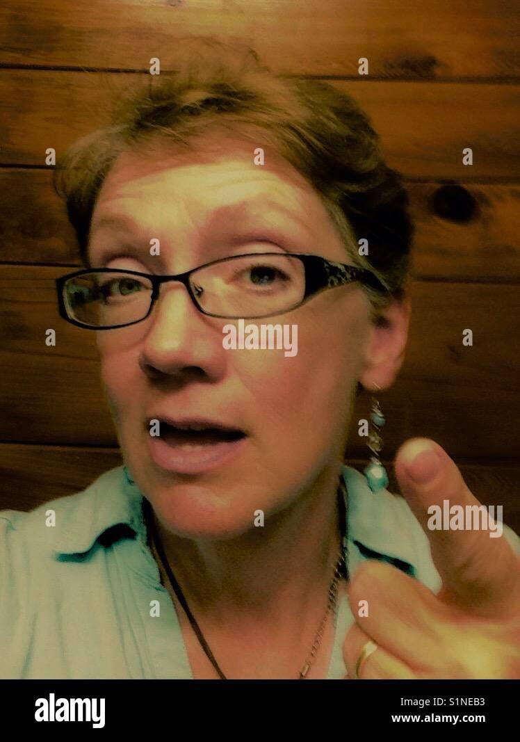 Mujer de mediana edad hace un punto con gesto conversacional Imagen De Stock