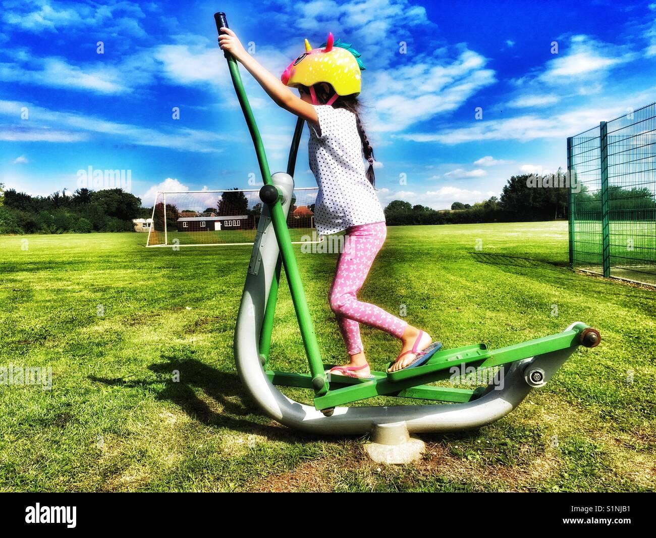 Chica utilizando máquinas de ejercicio público Imagen De Stock