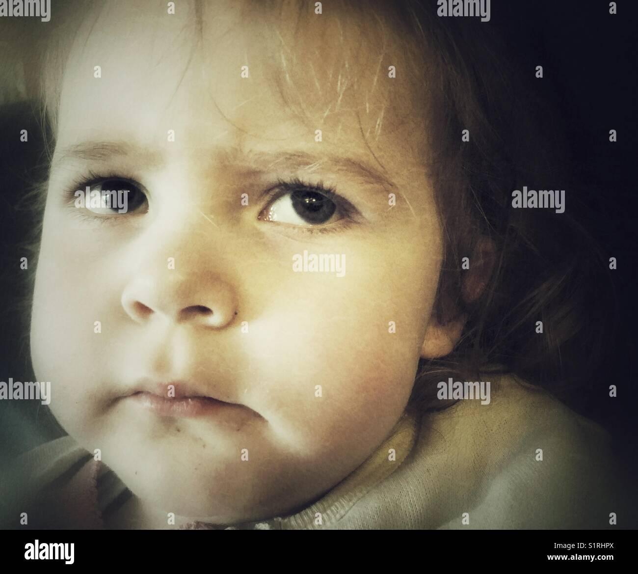 Moody closeup de niño niña cara con expresión temerosa mirando hacia arriba y al lado Foto de stock