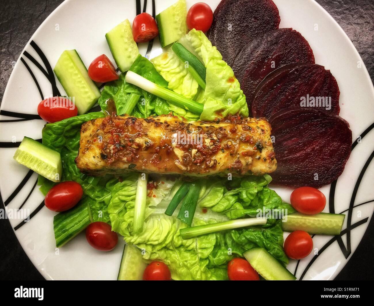 Bacalao Filete cubierto con una salsa de tomate y albahaca sentado en una cama de lechuga, tomates cherry con cebolletas, Foto de stock