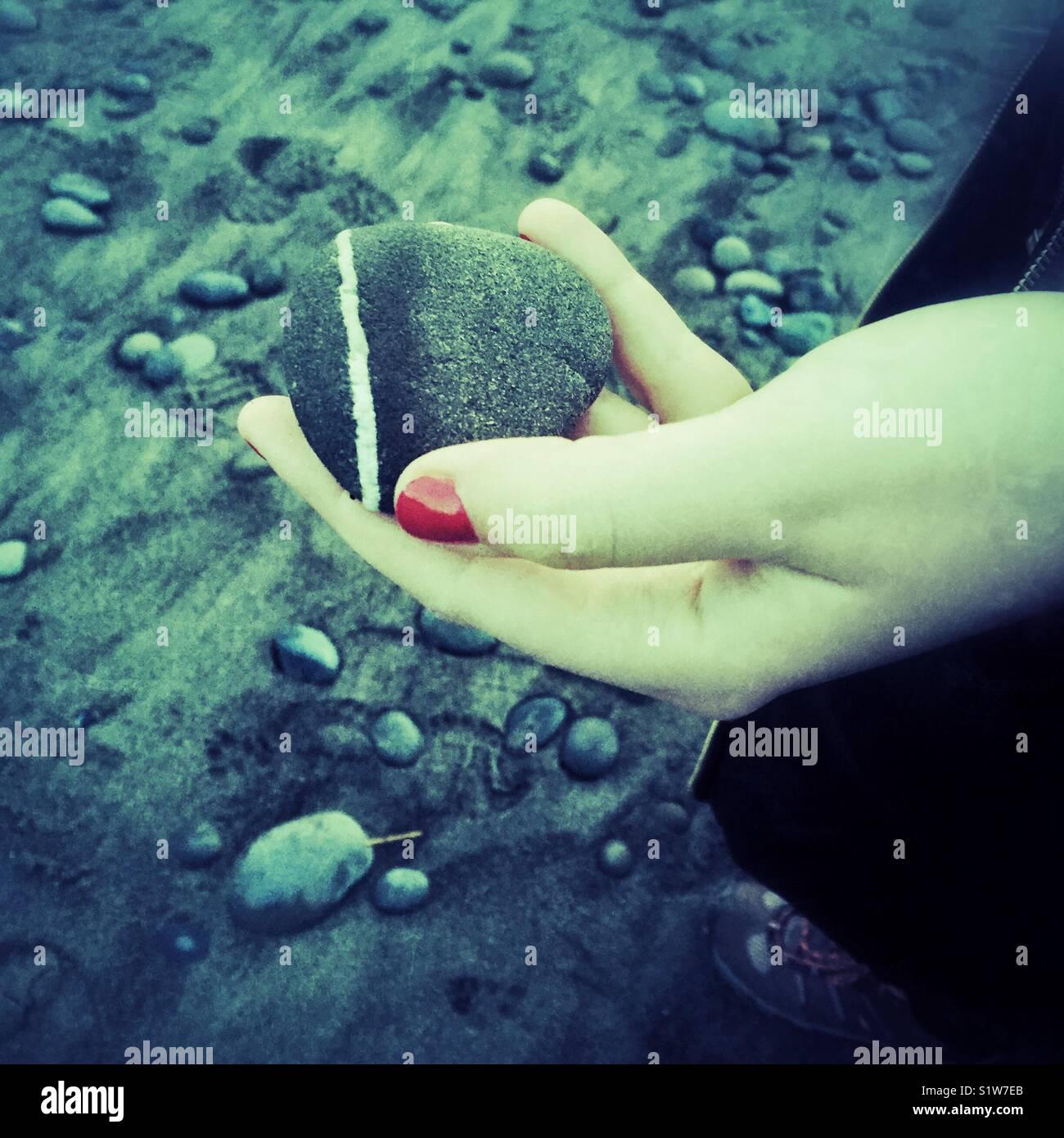 Mano con esmalte de uñas de color rojo sosteniendo la roca en una ...