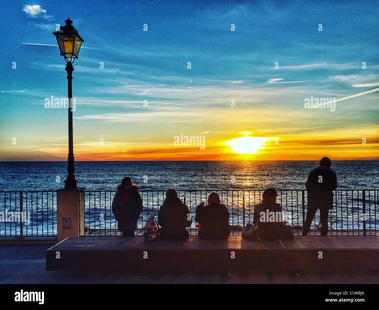 Cinco figuras recortadas contemple la puesta de sol sobre el Mediterráneo, Camogli, Italia Imagen De Stock