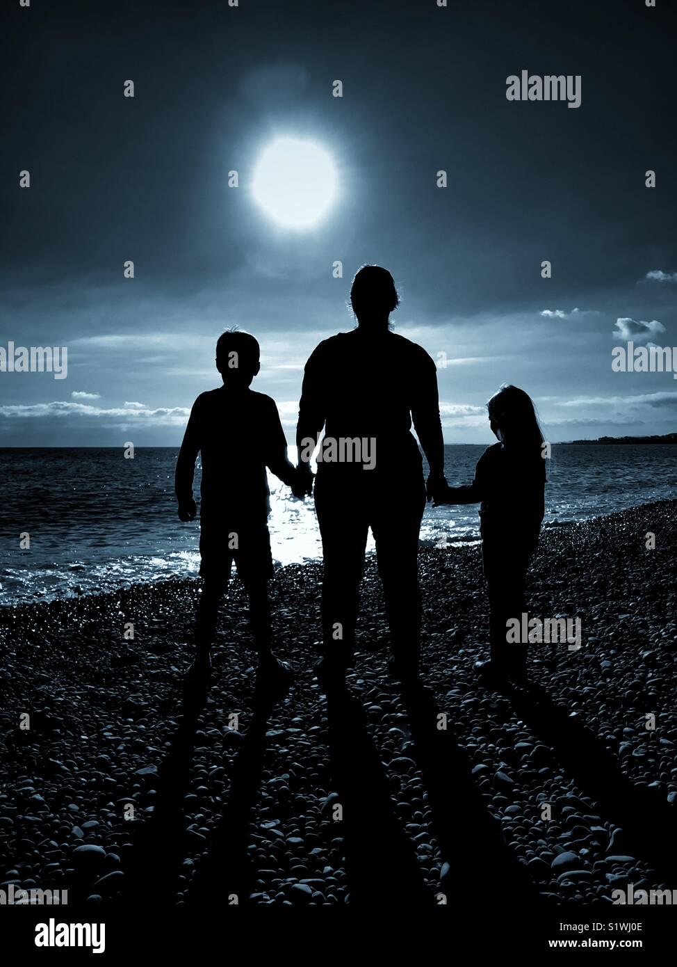 Las siluetas de 3 personas - una madre sostiene a las manos de sus 2 hijos como todos miran hacia una luz brillante. Imagen De Stock
