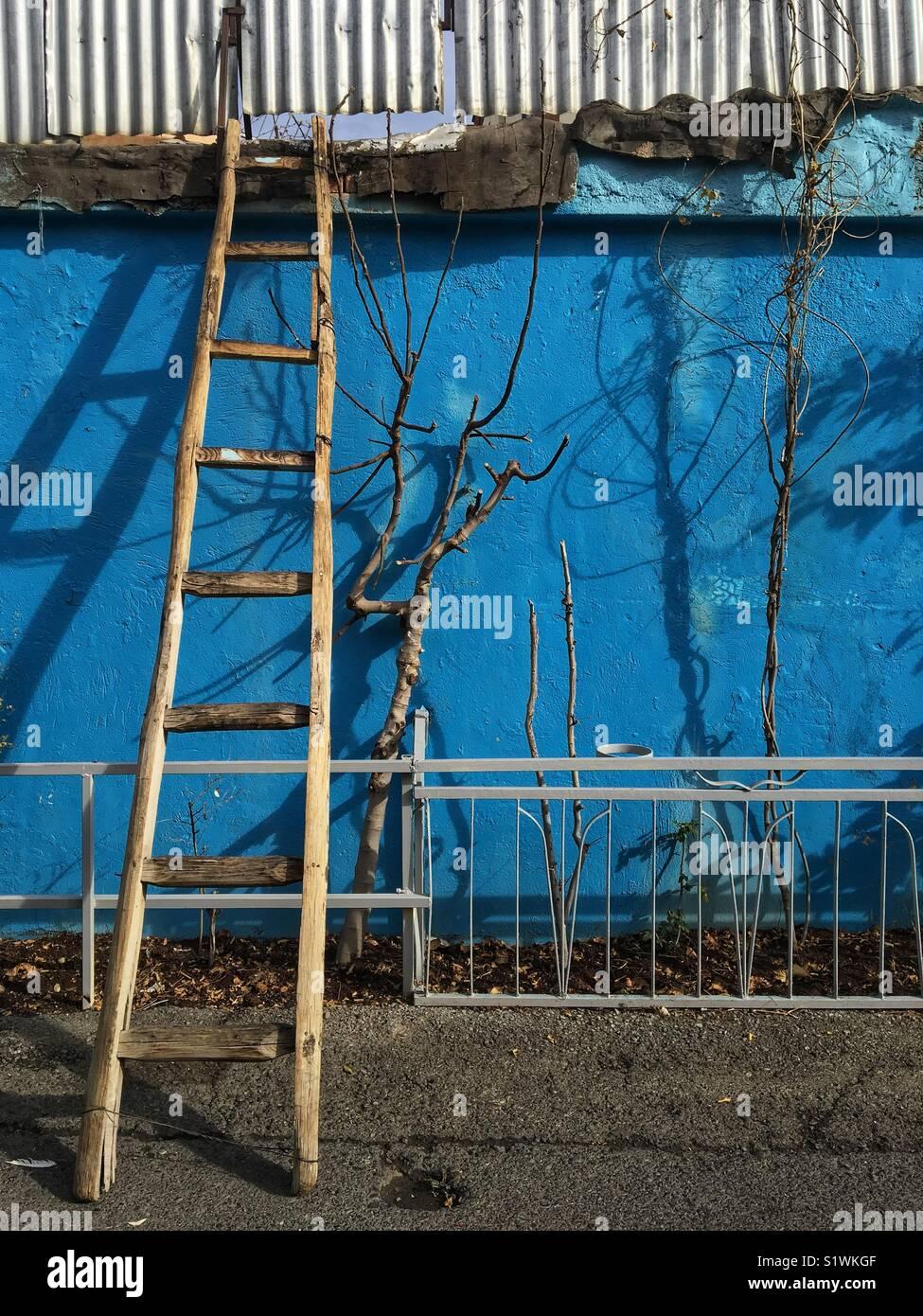 Una escalera en una pared azul. Imagen De Stock