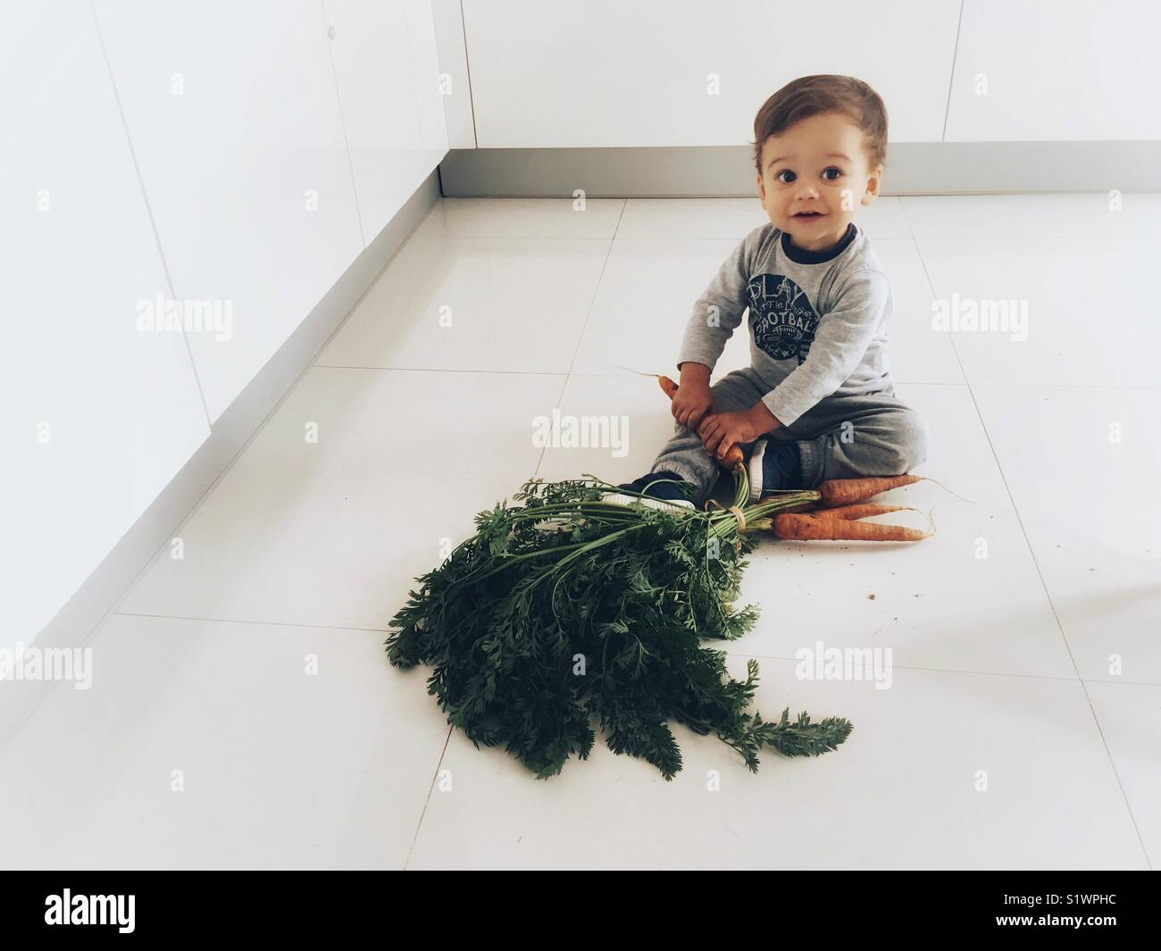 Un niño descubre las zanahorias. Imagen De Stock