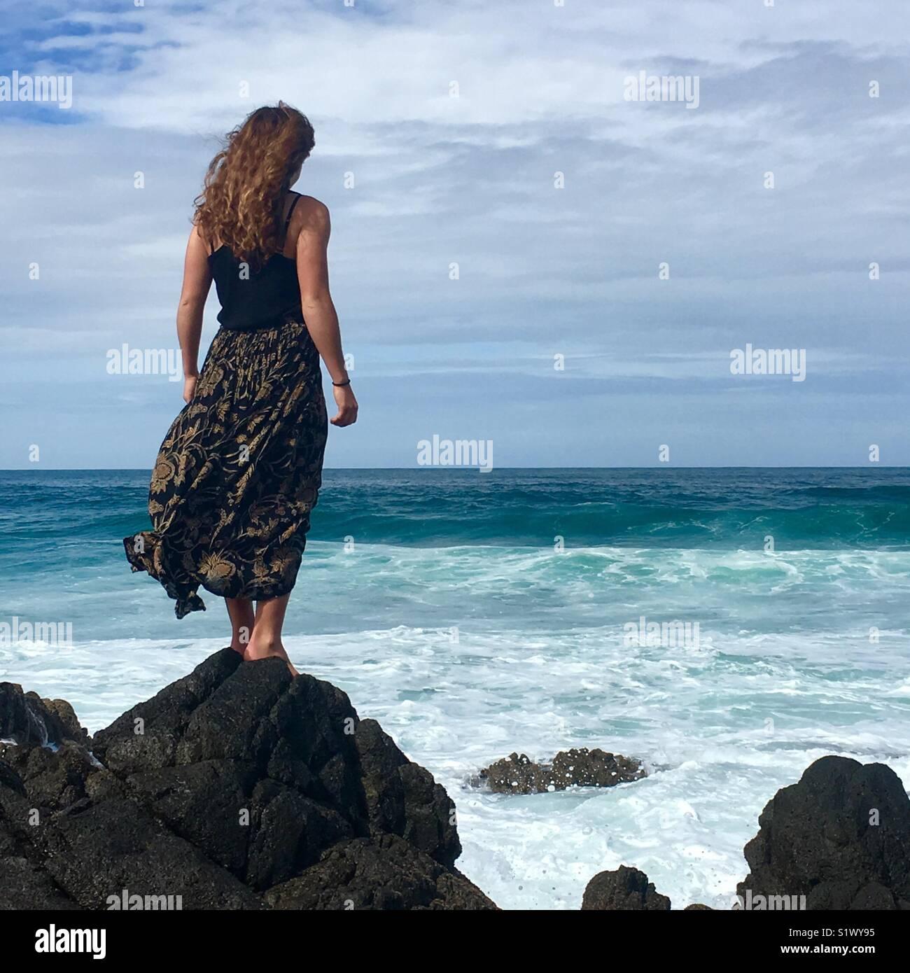 Chica se alza sobre una roca con vistas al mar Imagen De Stock