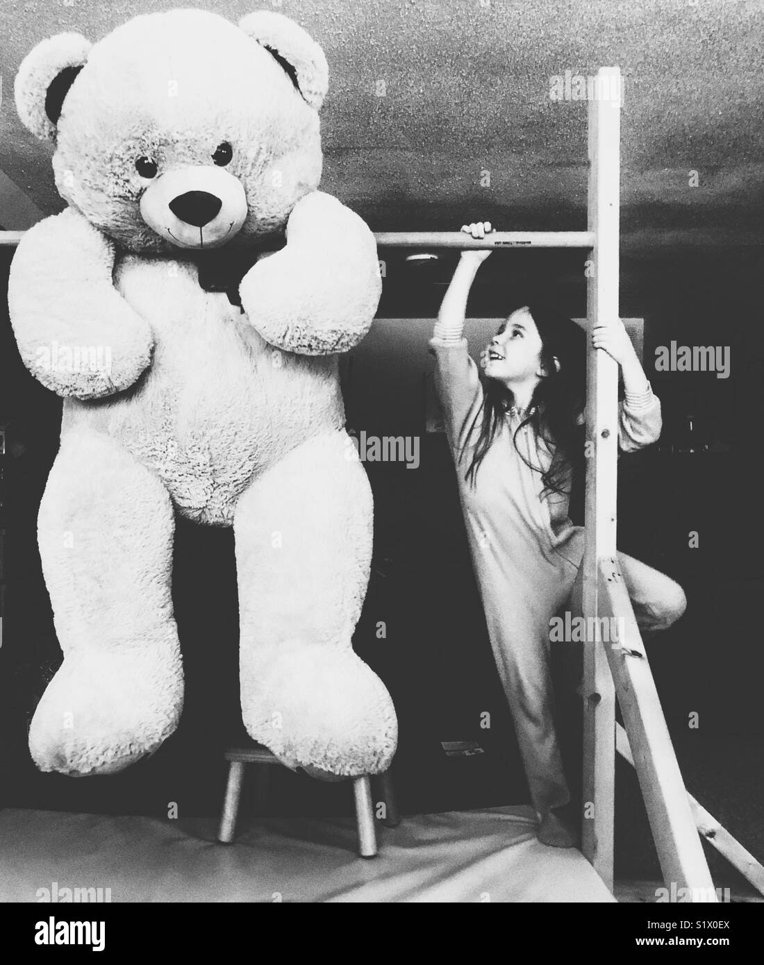 Muchacha con pelo largo en pijama Escalada de llegar a oso de peluche sobredimensionado gigante colgado en la barra Imagen De Stock