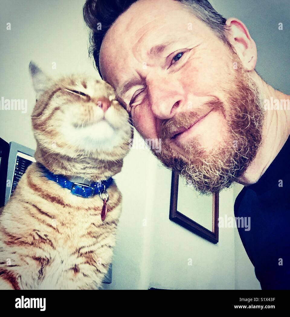 Feliz gato frota contra su propietario Imagen De Stock