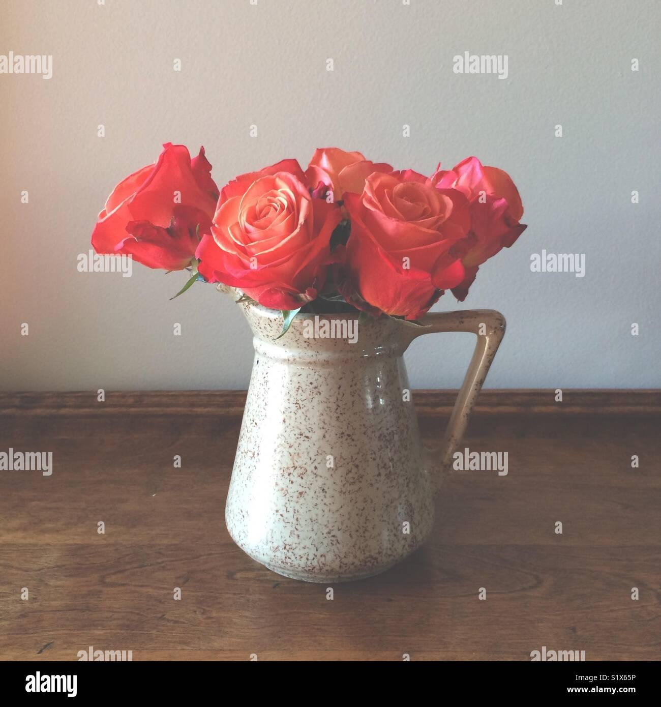 Naranja rojo rosas en una jarra Foto de stock