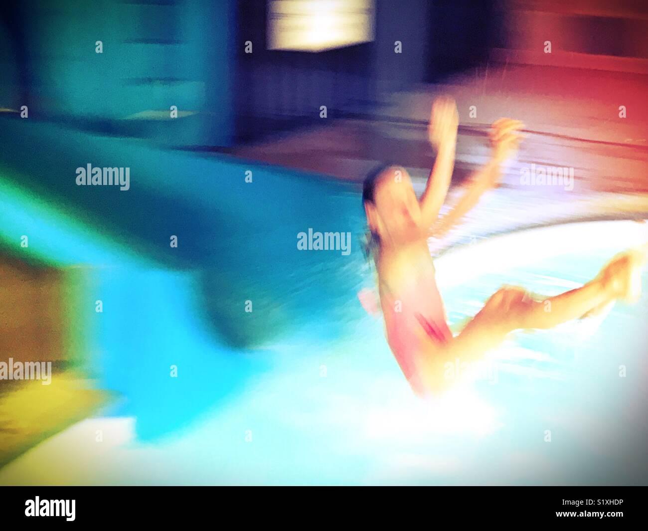 Una chica dispara fuera de un tobogán y roza sobre una piscina. Imagen De Stock