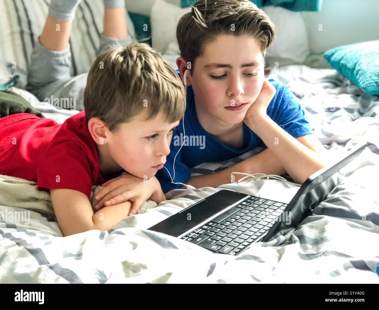 Dos muchachos viendo YouTube en una relajada tarde de domingo en el Reino Unido. Imagen De Stock