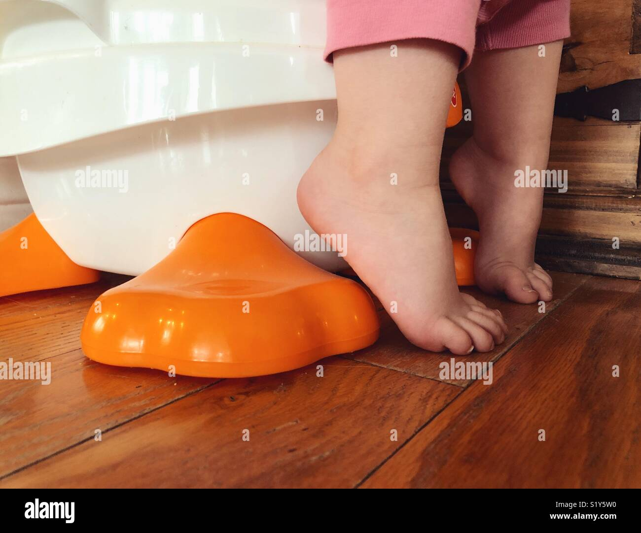 Closeup imagen del niño pies mientras esté sentado en el asientico con bacinica Imagen De Stock