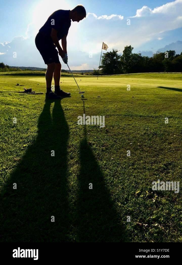 Golf en contraluz. Él va a jugar por un par? Imagen De Stock