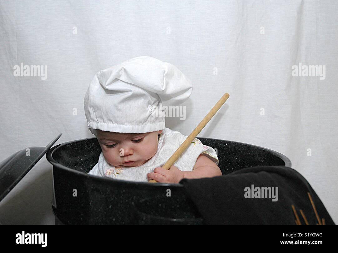 Un bebé juega con implementos de cocina. Imagen De Stock