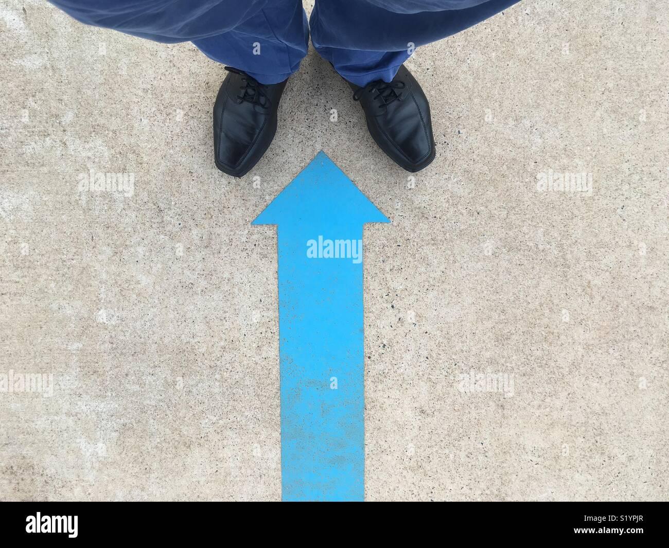 Una flecha azul pintada pintada en el suelo apuntando a un hombre negro zapatos y pantalones azules. Imagen De Stock