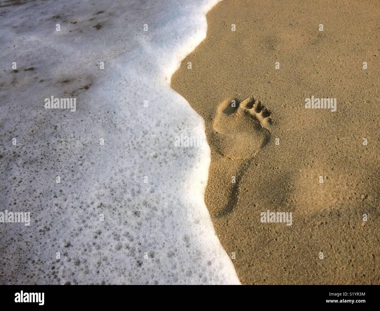 Footprint y olas en una playa de arena Imagen De Stock