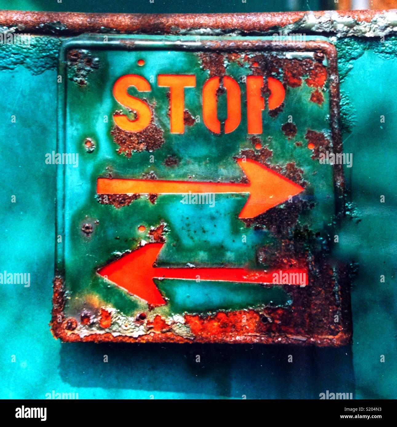 Cartel oxidado con la escritura de detener y flechas direccionales en ambas direcciones. Imagen De Stock