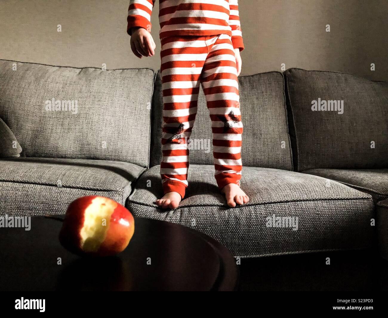 El niño con el pijama de rayas en el sofá con la mitad comido apple Imagen De Stock
