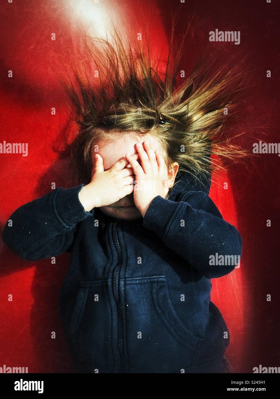 Niño Niña cubriendo la cara con las manos y el pelo que sobresale debido a la electricidad estática de una diapositiva de color rojo Imagen De Stock