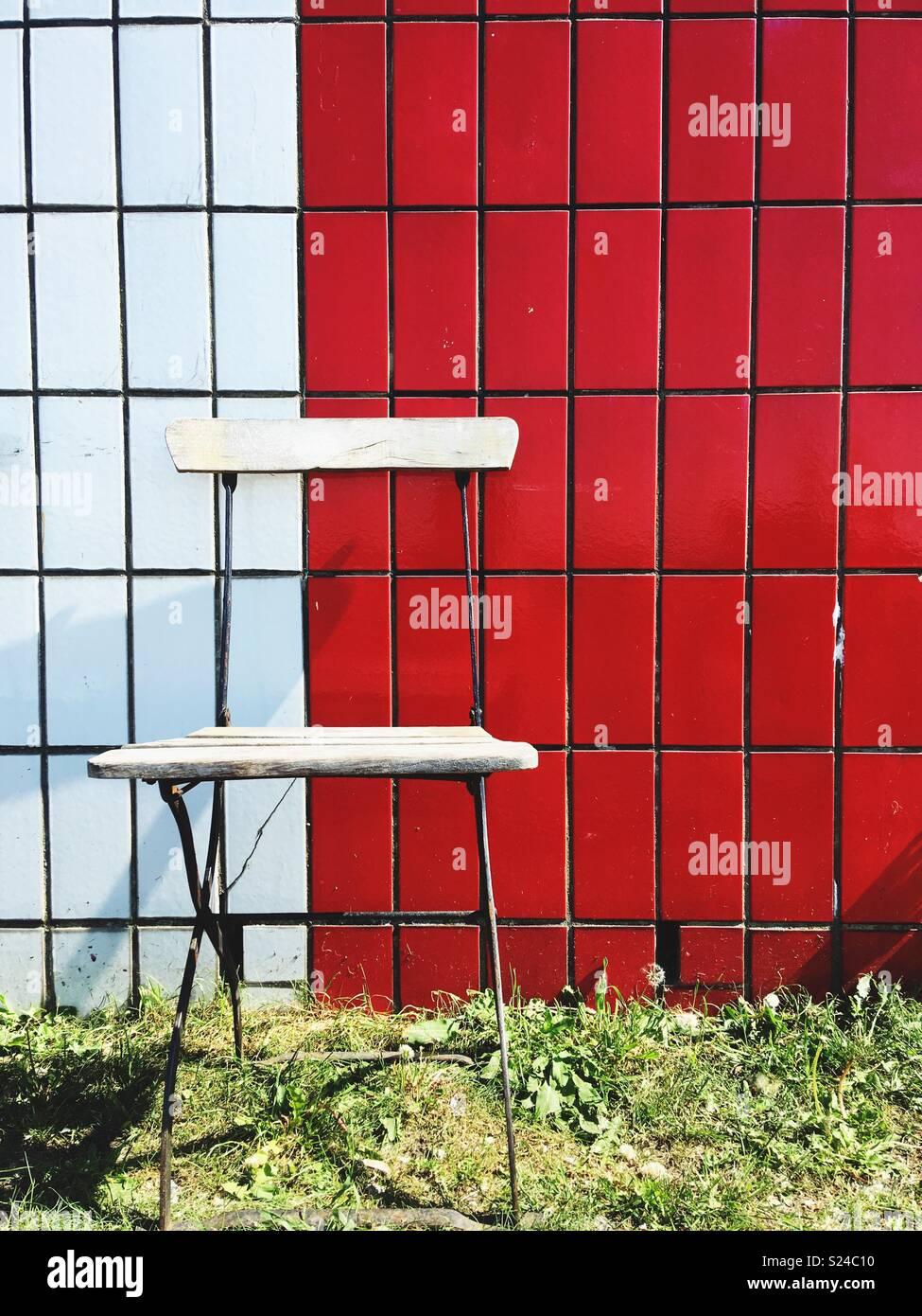 Una silla de jardín de madera contra una pared de baldosas rojas y blancas Imagen De Stock