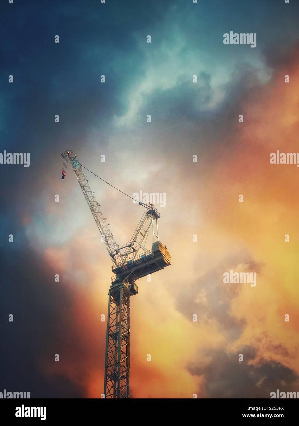 Una grúa en la ciudad de Londres contra un cielo de colores brillantes Imagen De Stock