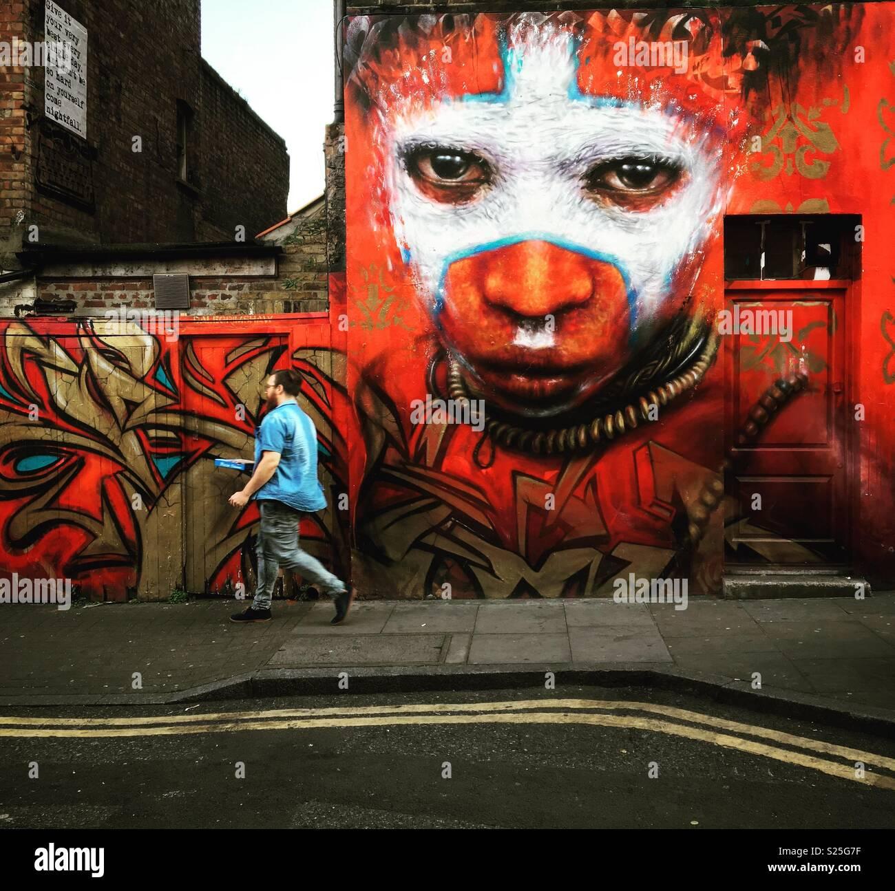Guy caminando por edificio con arte callejero en East London Imagen De Stock