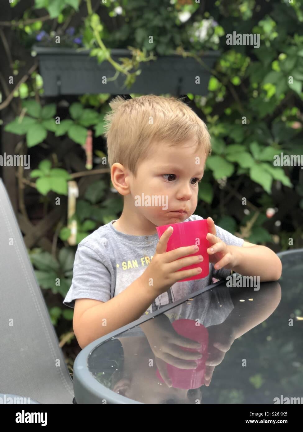 c1152e5c3c340 Un niño de beber agua de una cubeta de plástico rosa en el porche de atrás