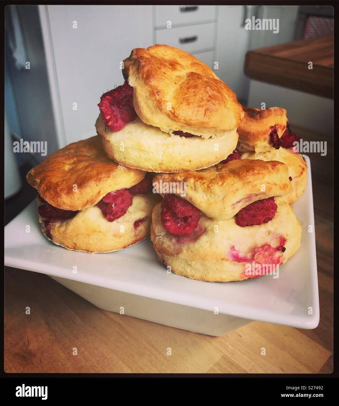 Frambuesas frescas scones clama ser sofocados en coagulado crema y comido Imagen De Stock