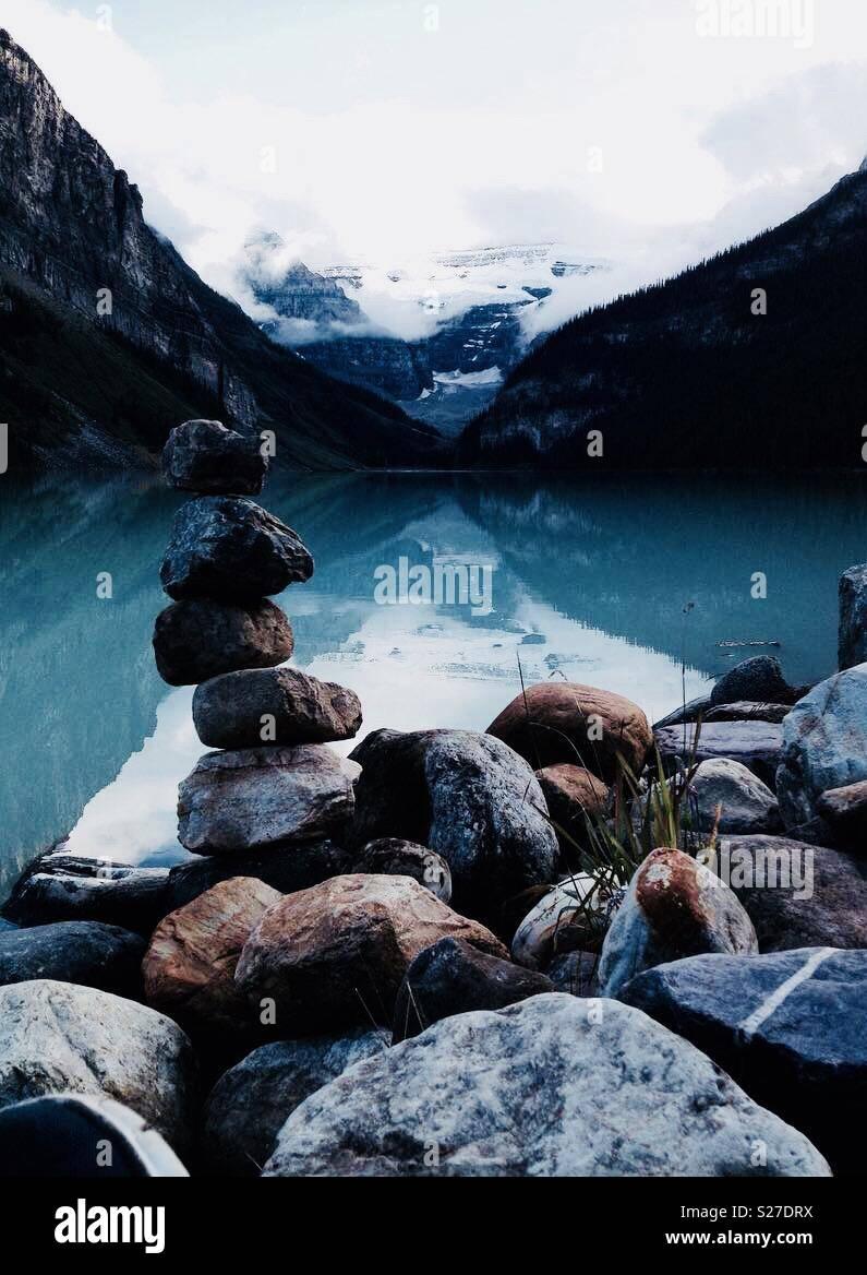 Inukshuk rocas apiladas en Lake Louise, con picos nevados en el fondo Imagen De Stock