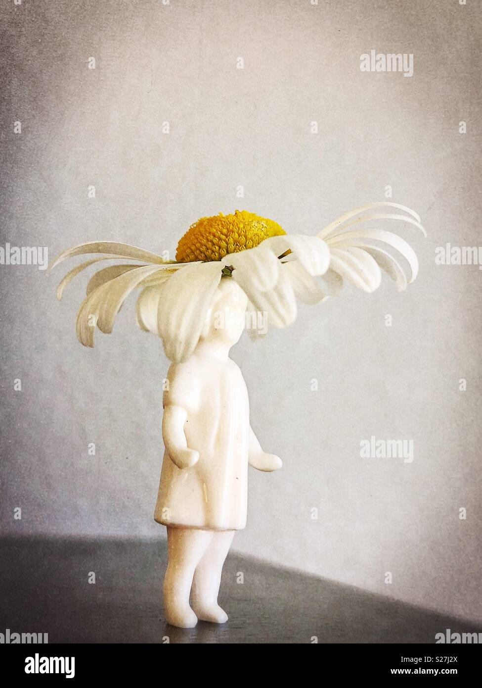 Figurilla de una niña con sombrero de margarita. Imagen De Stock