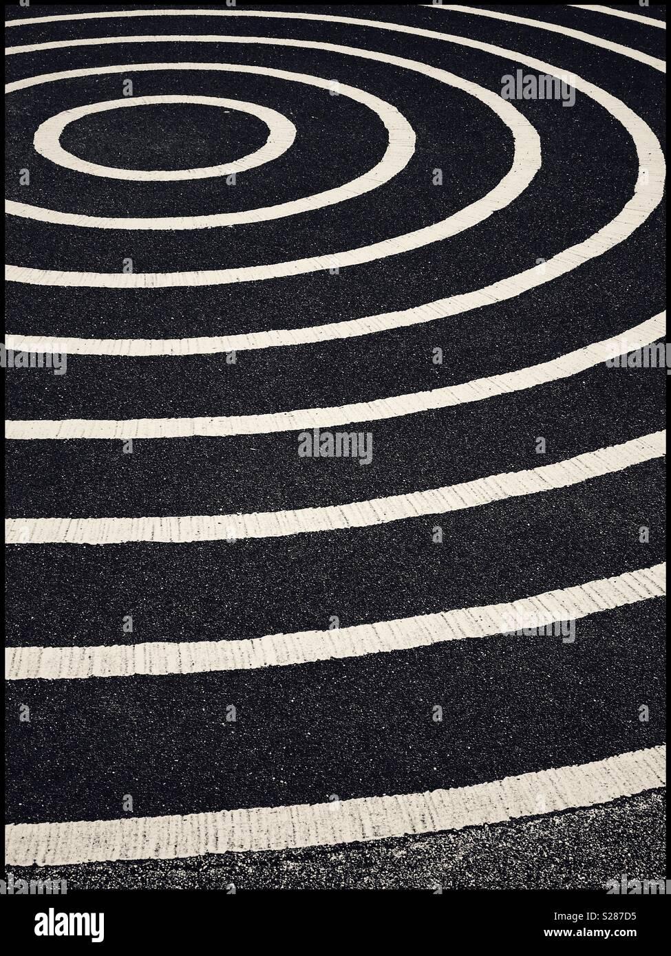 Un gráfico, imagen monocroma de círculos concéntricos, pintadas sobre una gran superficie de asfalto (asfalto). Una imagen con múltiples usos potenciales. Crédito de la Foto: © COLIN HOSKINS. Imagen De Stock
