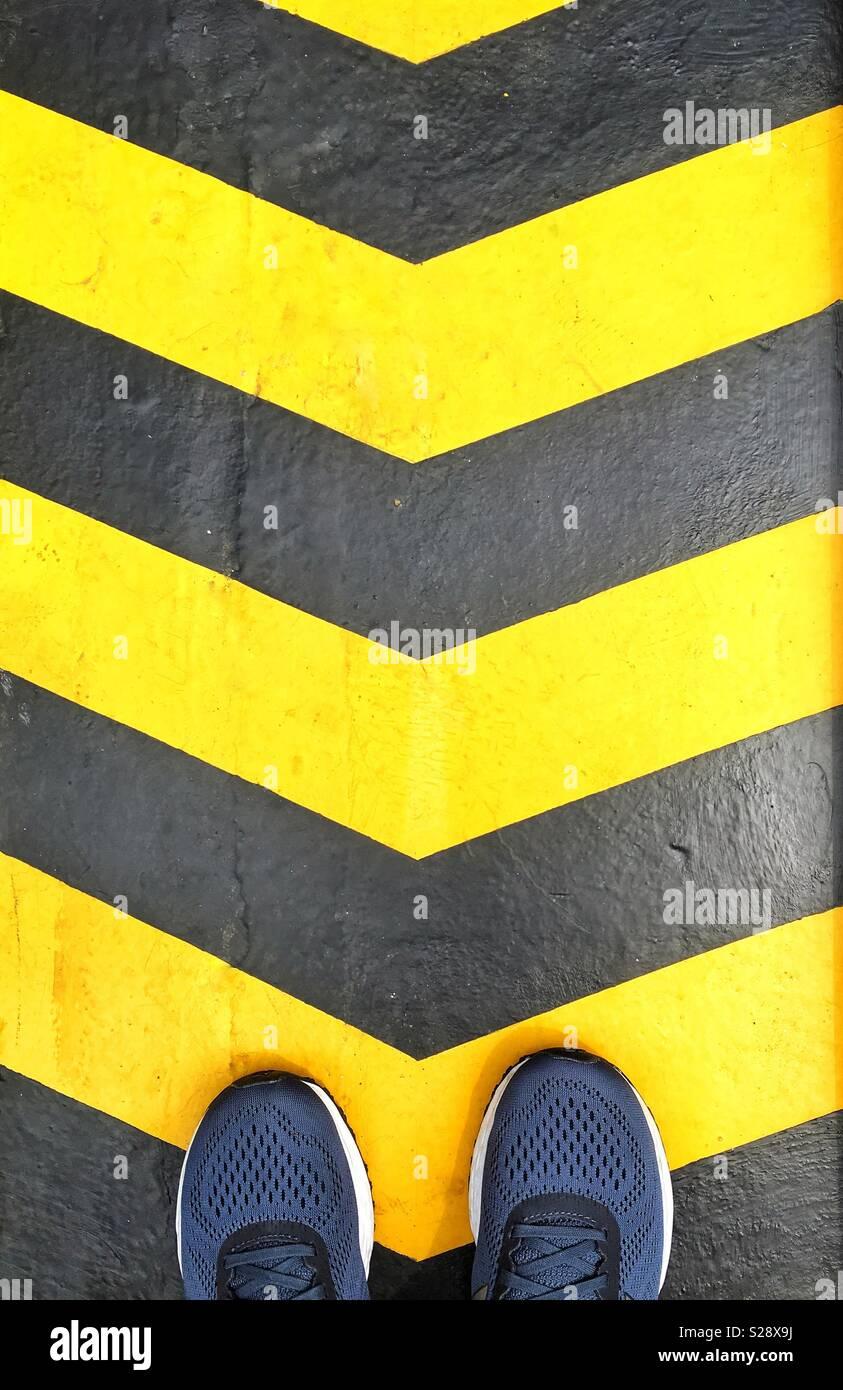 Concepto de dirección. Flechas pintadas de amarillo y negro mirar los zapatos de pie en ellos. Imagen De Stock