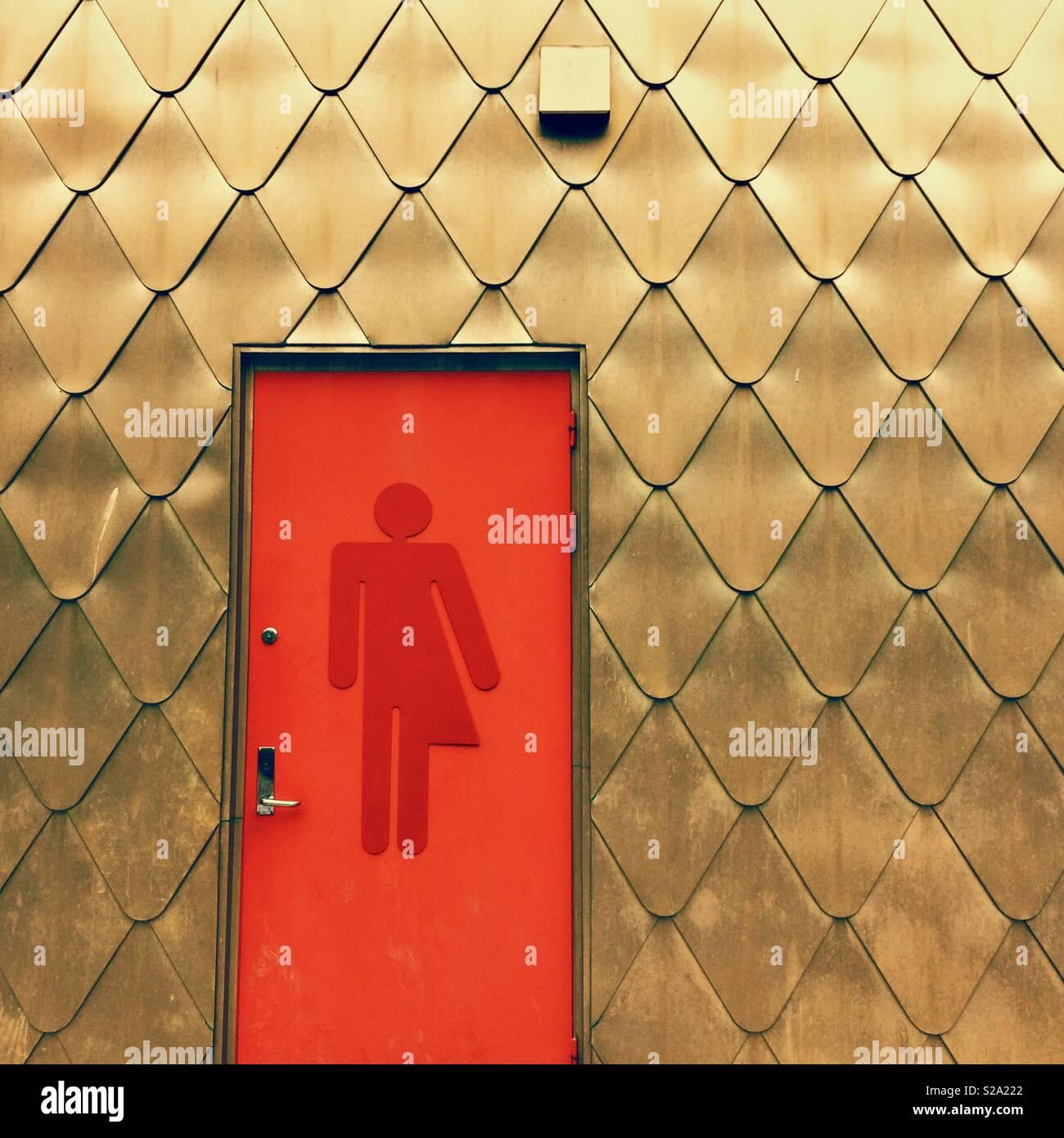 Una puerta de baño unisex rojo en un edificio - Oro líquido de género / género neutro / símbolo transgénero Foto de stock