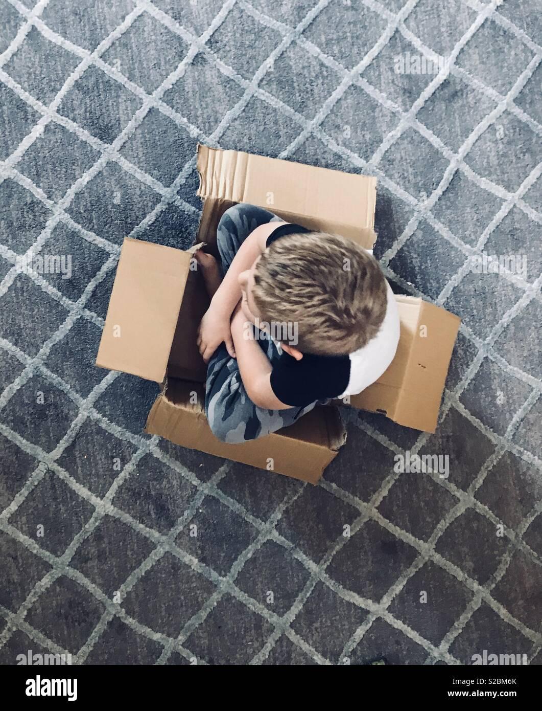 Niño sentado en su auto de carrera caja de cartón viendo la televisión, jugando a fingir Imagen De Stock