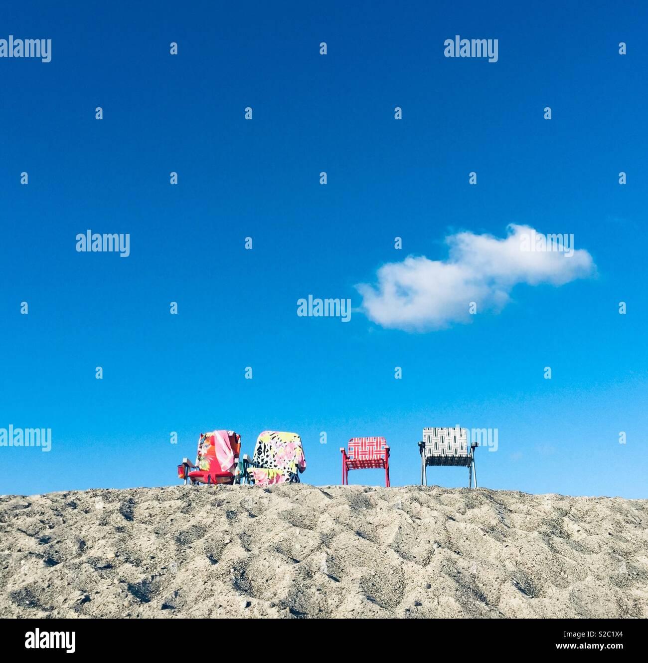 Cuatro coloridos sillas de playa, sentarse sobre una duna de arena en Capo Beach en el condado de Orange, CA. Imagen De Stock