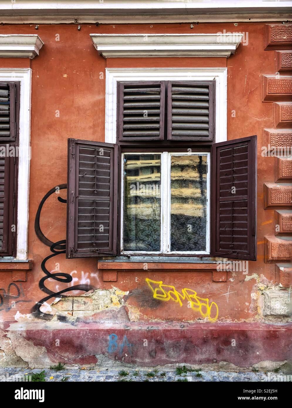 Marrón abierta ventana postigos, reflexión y graffiti en una pintura en la pared. Foto de stock
