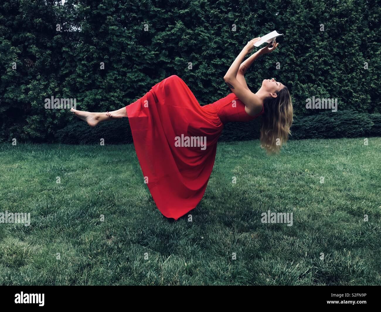 Chica en vestido rojo volando con el libro Foto de stock