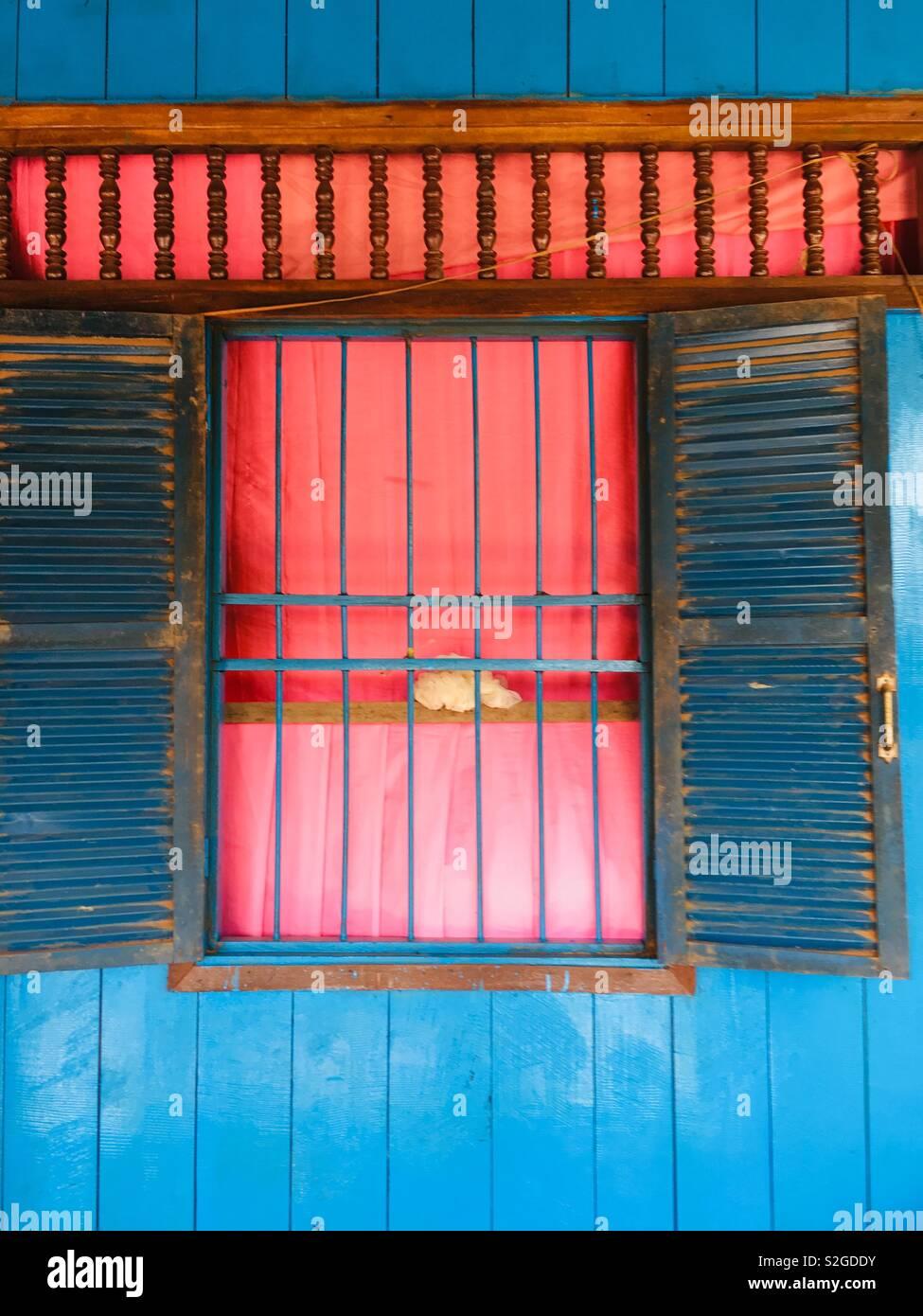 Ventana con rejilla de metal y tiempo gastado persianas establecido en una colorida casa de madera pintada. Camboya El Sudeste asiático Foto de stock