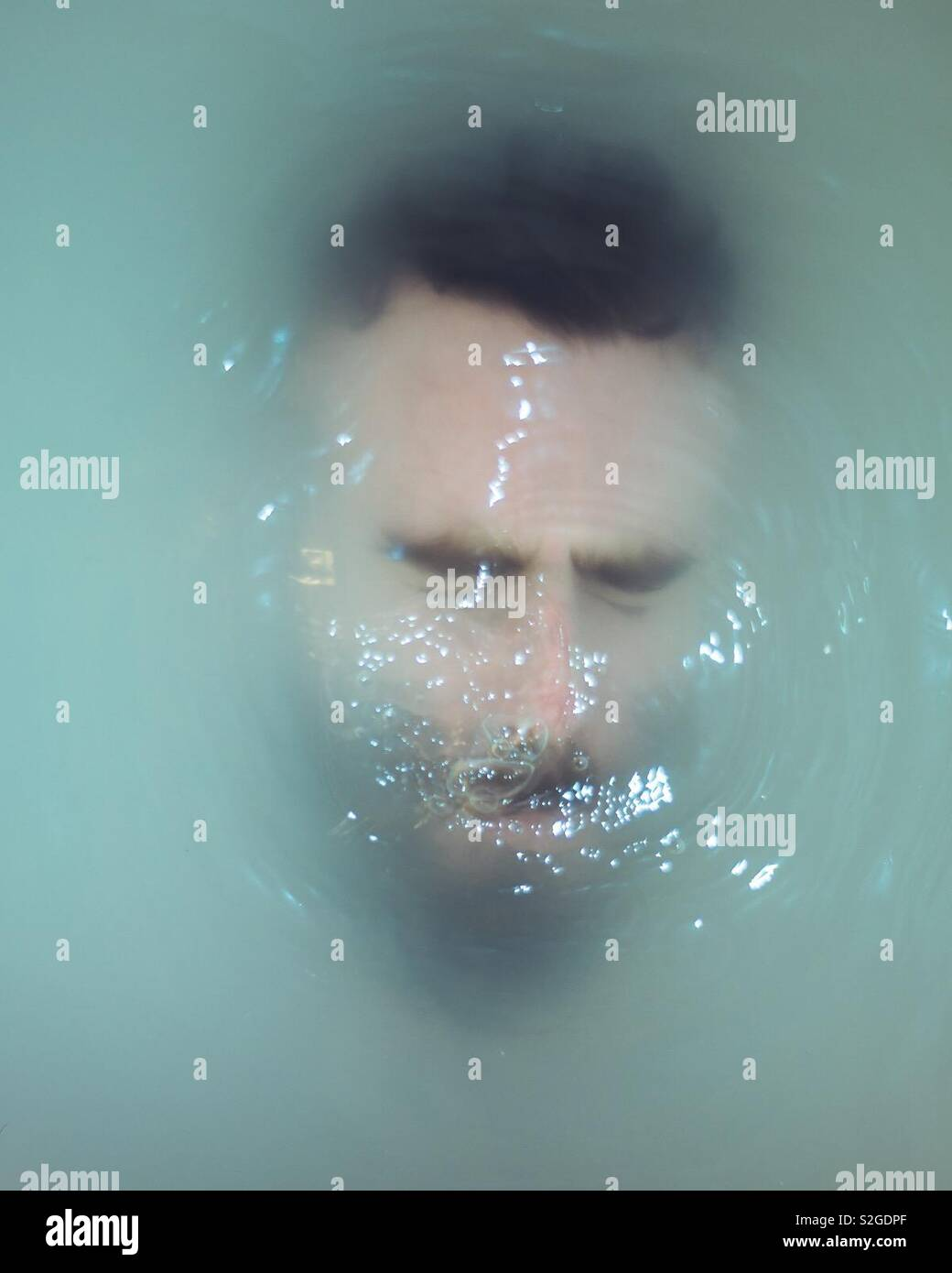 Chico con barba y ojos cerrados está sumergido bajo el agua de color lechoso. Foto de stock