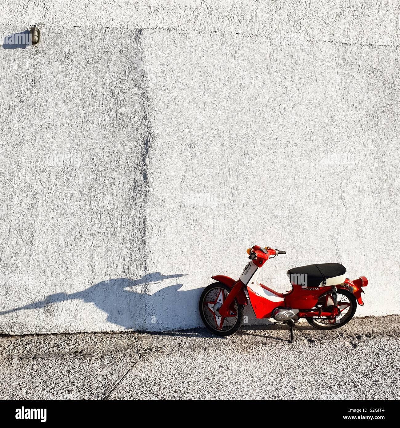 Scooter roja y blanca pared en Isla de Milos, Grecia Foto de stock