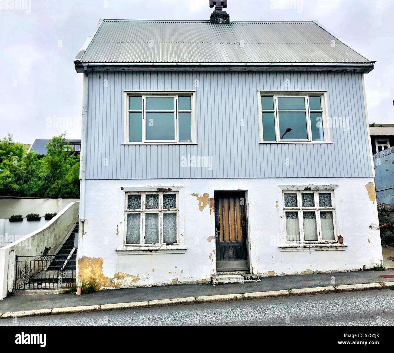 Una casa de color azul pálido con cuatro ventanas en las Islas Feroe. Foto de stock