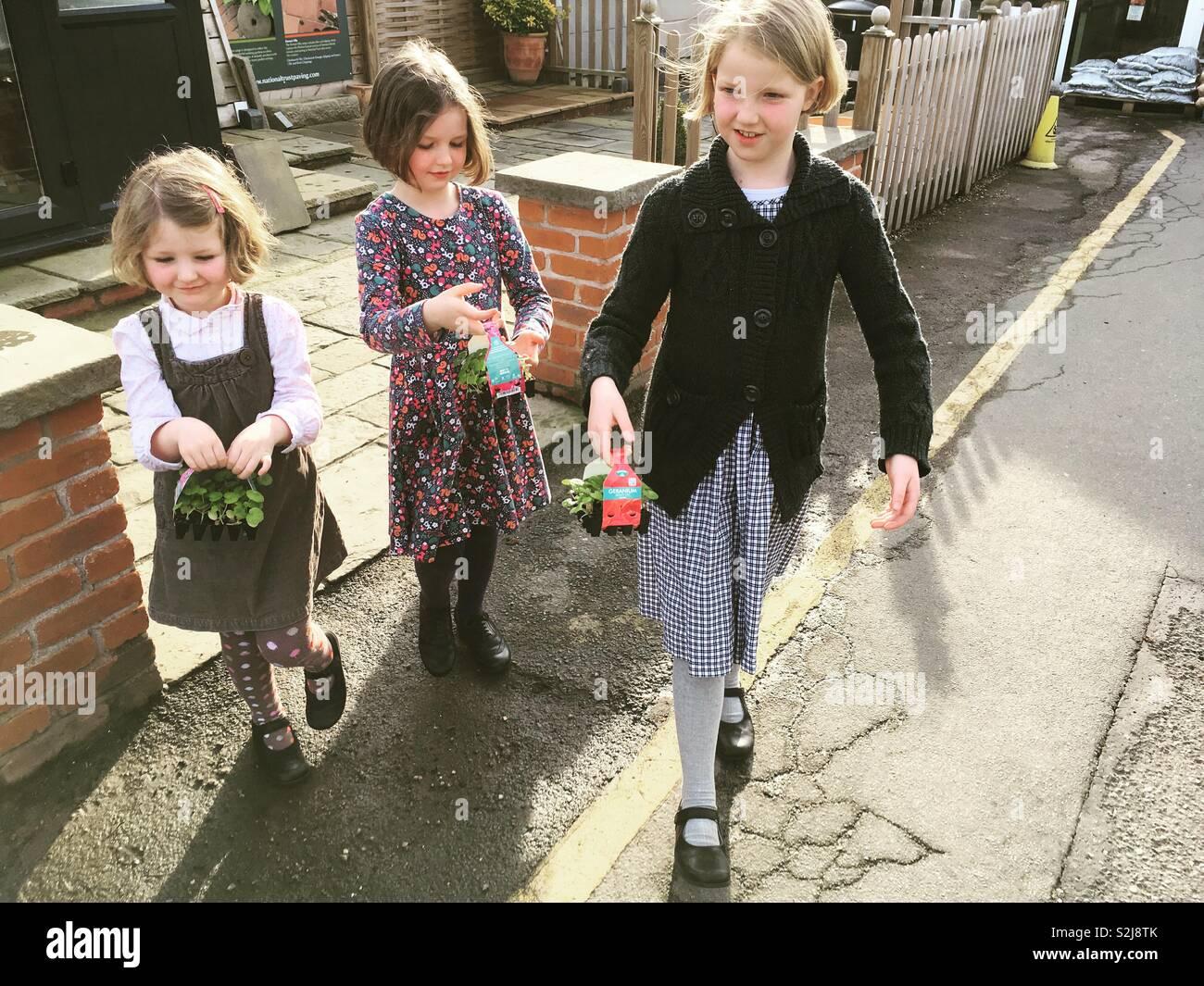 Niños, niños, niños, hermanas, jóvenes jardineros dejando un jardín central con las plántulas / bandejas de plantas que acaban de comprar comprado. Uk Foto de stock