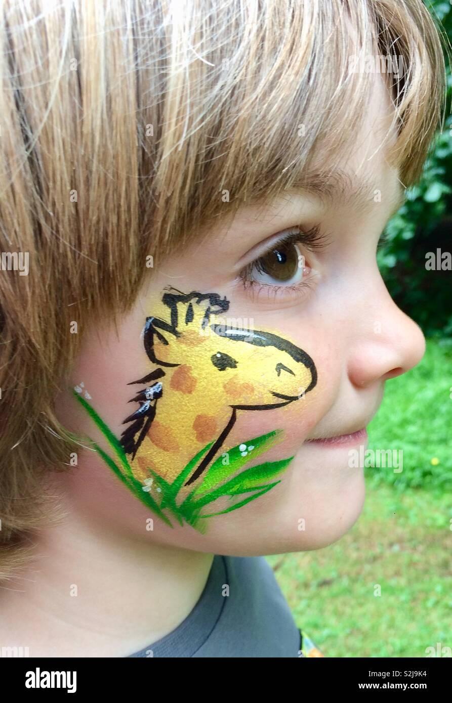 Chico con jirafas pintura facial Foto de stock