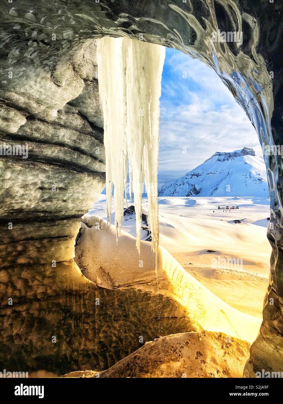 Katla hielo glaciar cueva cerca de Vik, Islandia mostrando un gran carámbano nee la entrada a la cueva mirando hacia las montañas cercanas. Foto de stock
