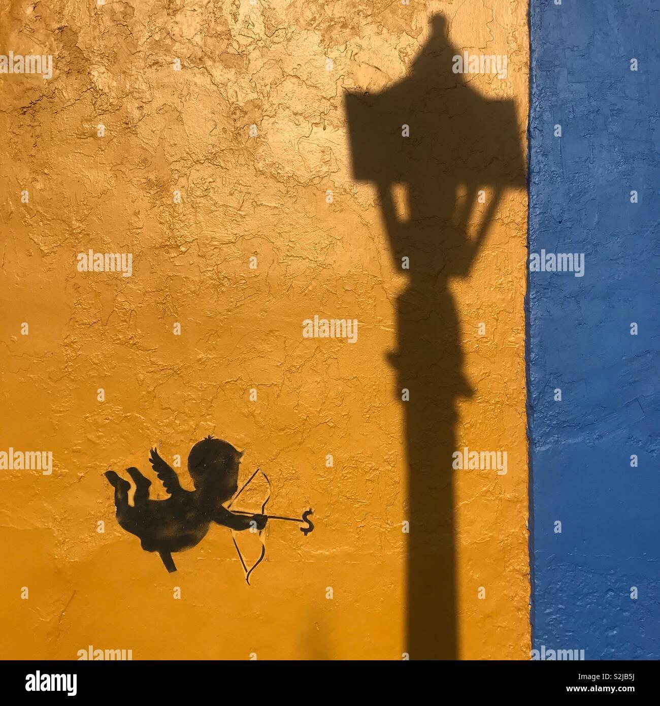 Una lámpara de la calle sombra se proyecta sobre una pared cerca de una pegatina naranja de un cupido apuntando con su flecha a un signo de dinero ($) en Oaxaca, México Imagen De Stock