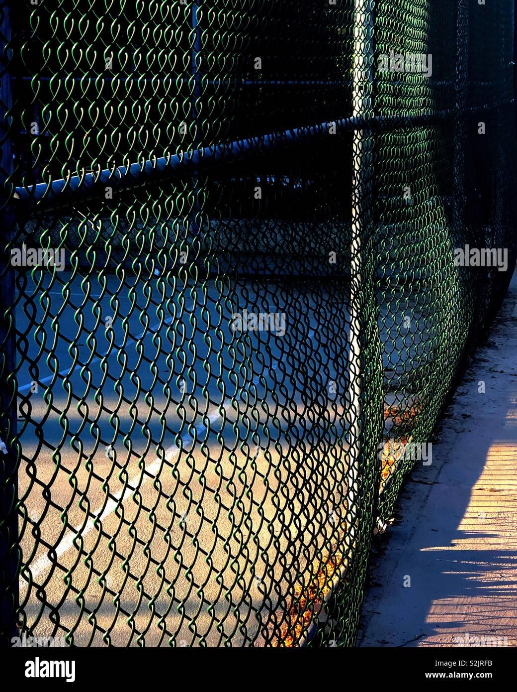 Amanecer proyecta sombras en una cancha de baloncesto y la valla que lo rodea Foto de stock