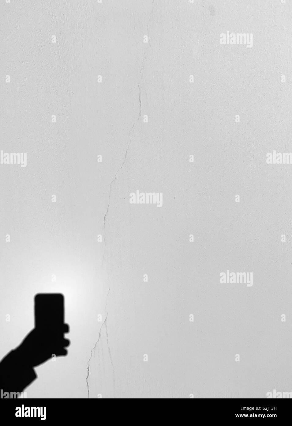 Una sombra de una mano sujetando un teléfono celular. Foto de stock