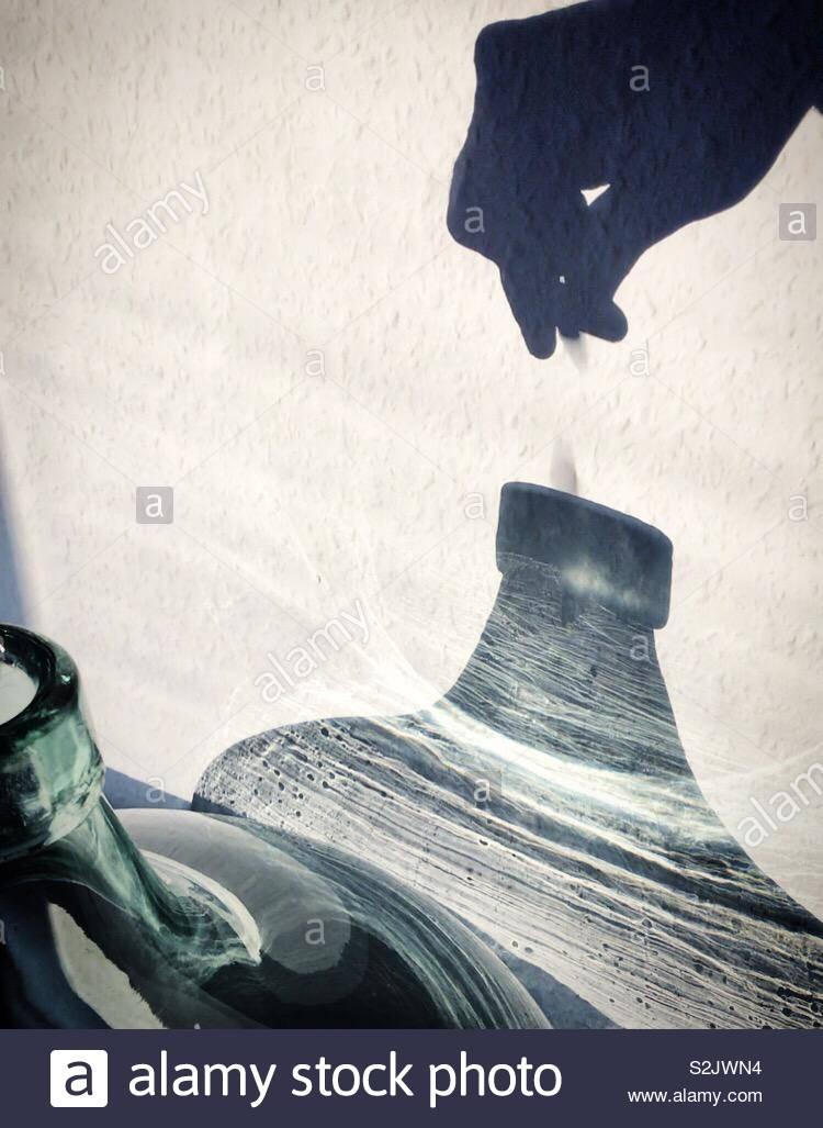 Muro de sombra mano colocando una moneda en un tarro de vidrio. Imagen De Stock