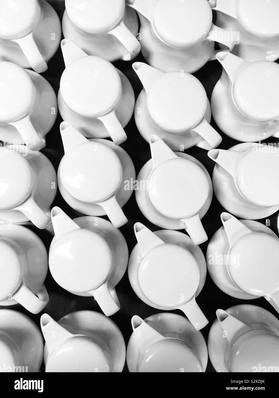Grupo de ollas de té blanco en las filas de arriba. Formulario de formas y patrones, mirando hacia abajo en varias blanco sobre negro, teteras, mesa de restaurante o cafetería de fondo. Foto de stock