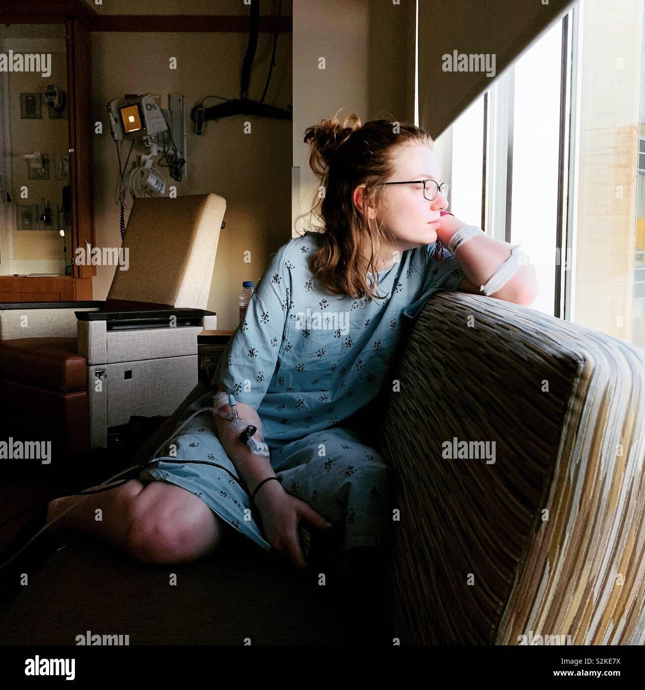 Chica en un hospital mirando por la ventana Foto de stock